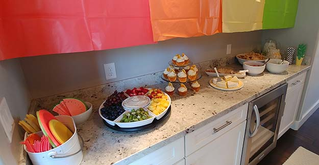 One in a Melon First Birthday Party Food Bar with Fruit Platter, Orange Creamsicle Cupcakes, Cheeses, Salsa, and Guacamole